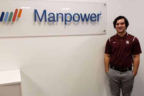 "student in front of ""Manpower"" sign"