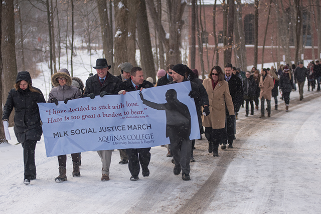 Large group of people marching in the snow holding MLK banner