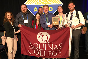 "students holding an ""Aquinas College"" flag"