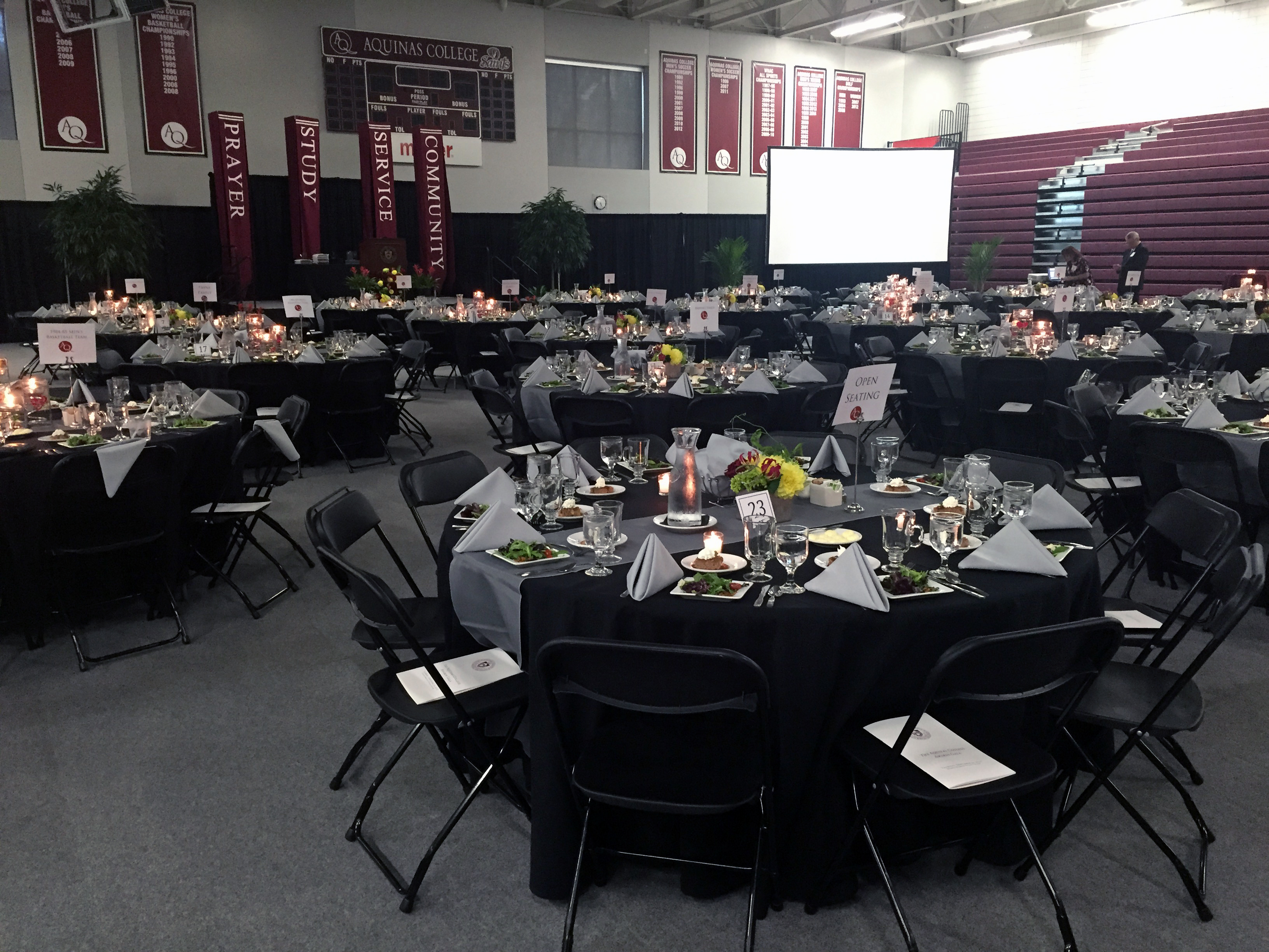 tables set up with fancy dinner decor in the gym