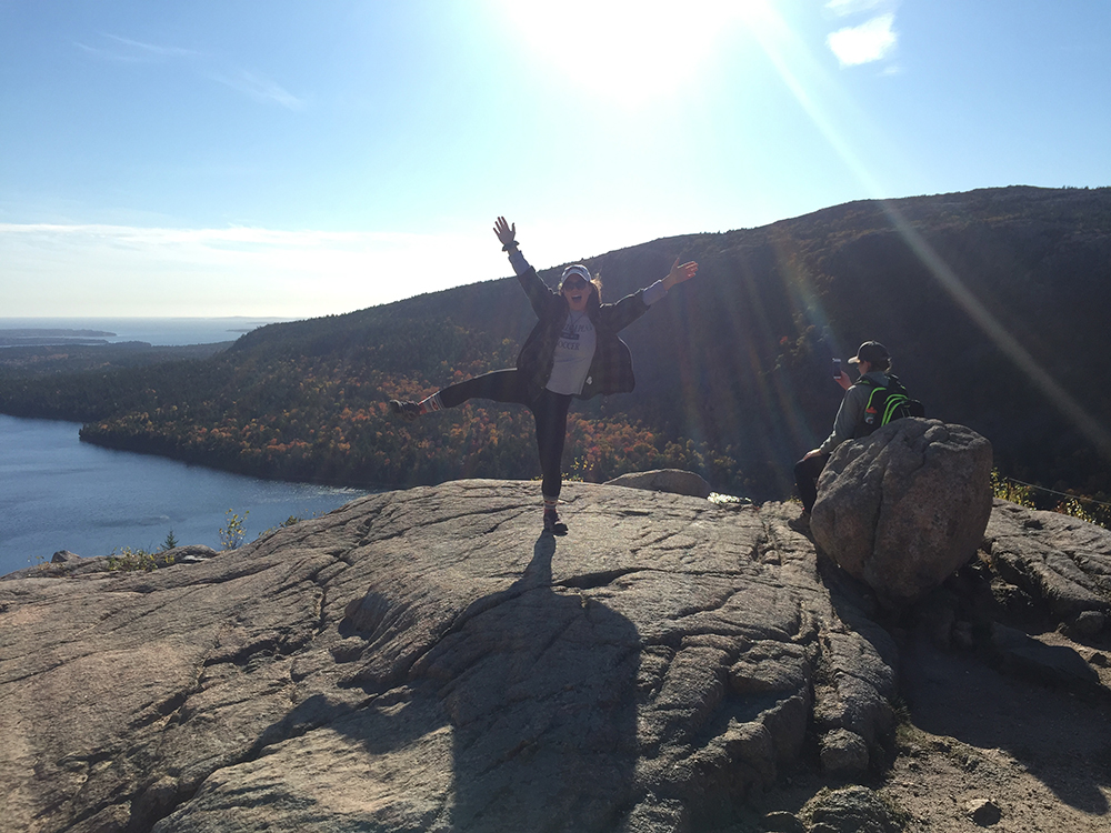 woman standing on one foot on top of rock