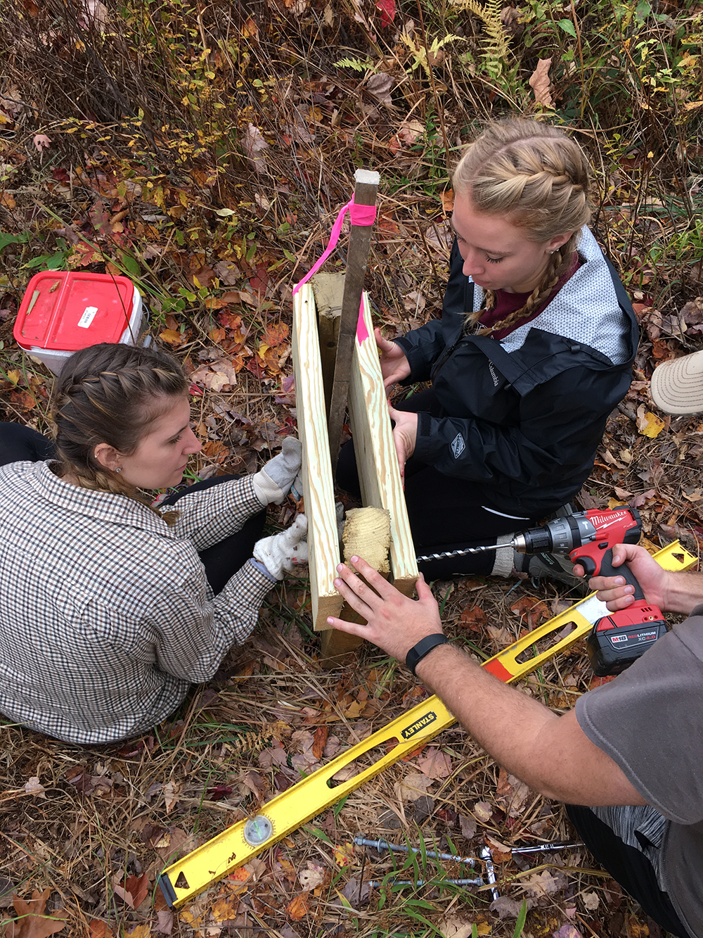 two students building something out of wood