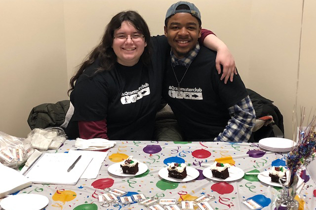 two students serving cake wearing AQ commuter club tshirts