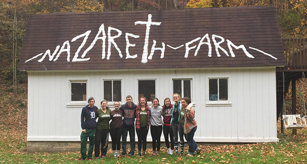 "students on a service learning trip with ""Nazareth Farm"" painted on the roof"
