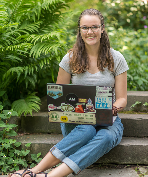 student sitting on stairs using laptop outside