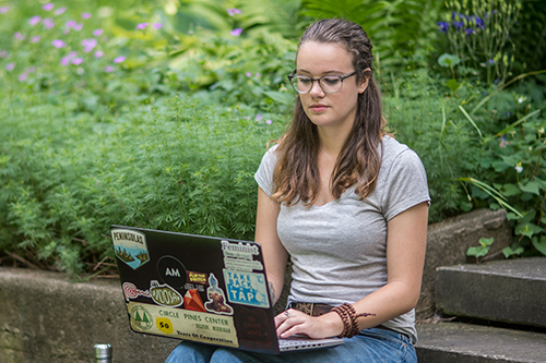 student working on laptop outside