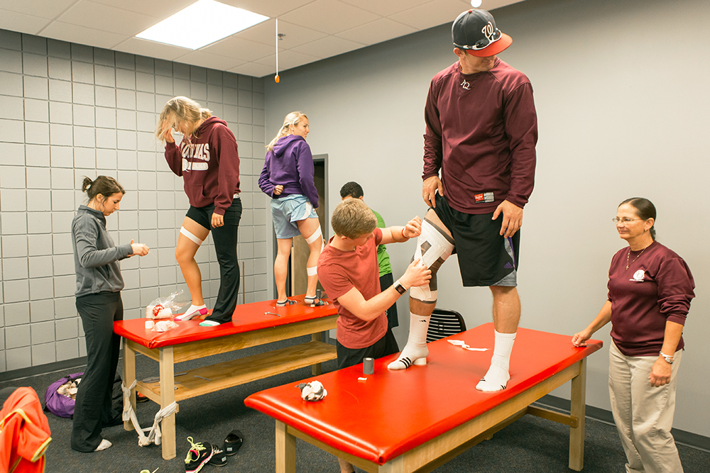 students putting braces on knees in a training room