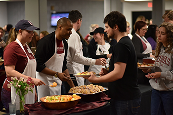 workers in cafeteria serving food to students