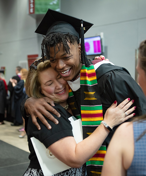 student and adult hugging after gradation