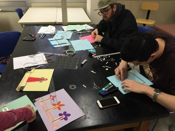 students working at a table with crafts