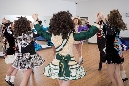 Students dancing mid air in Irish Dance costumes