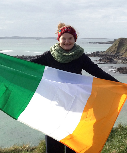 student with Irish flag by cliff
