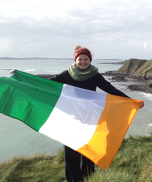 student holding Irish flag on coast