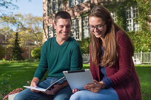 two students outside working on computer