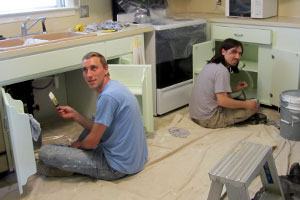 two people painting in a kitchen
