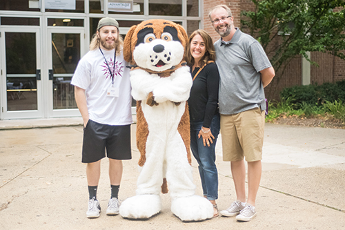 student, parents, and mascot standing outside a dorm