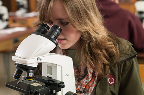 student looking in microscope