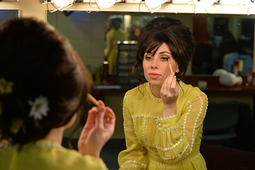 student doing makeup in mirror