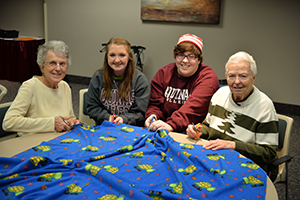 students and sisters making a blanket