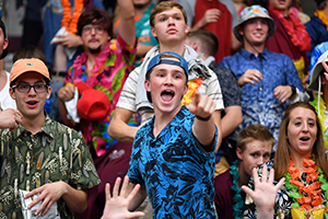student in stands yelling surrounded by other students wearing colorful shirts