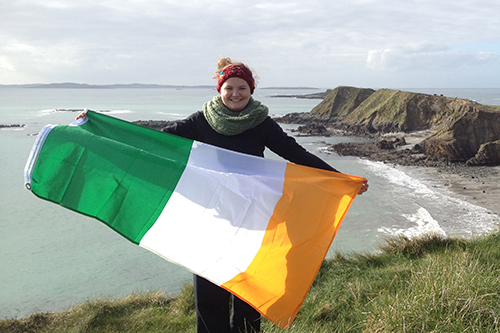 student standing on cliff holding Irish flag