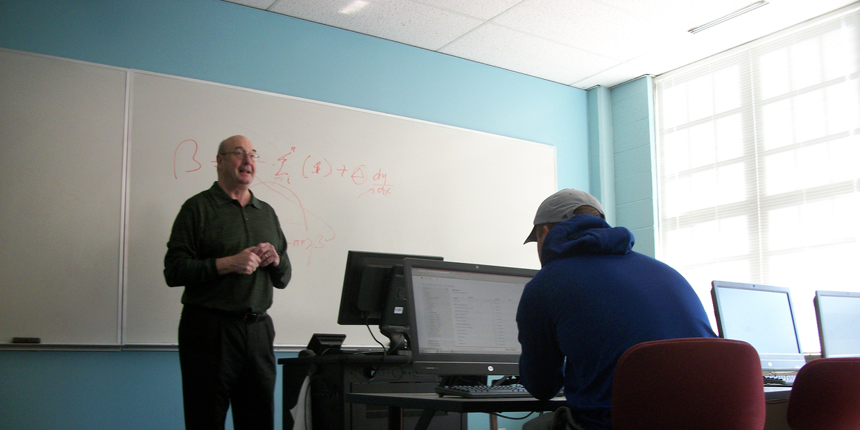 student working on computer and a professor teaching