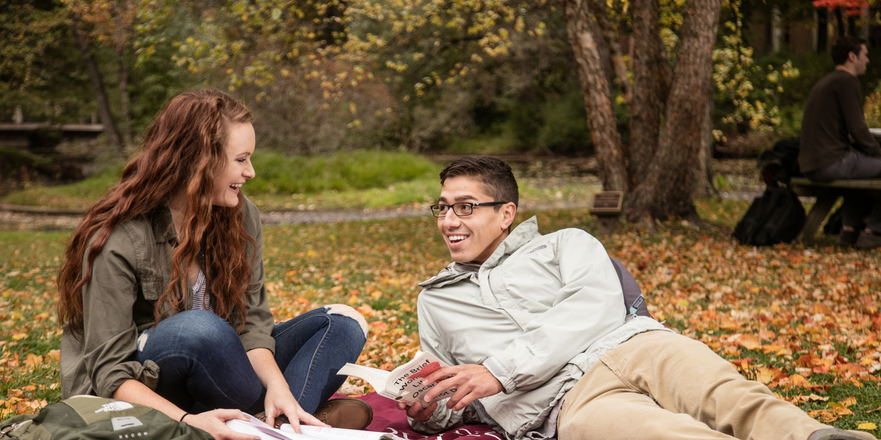 a boy and a girl sitting on the ground in the fall
