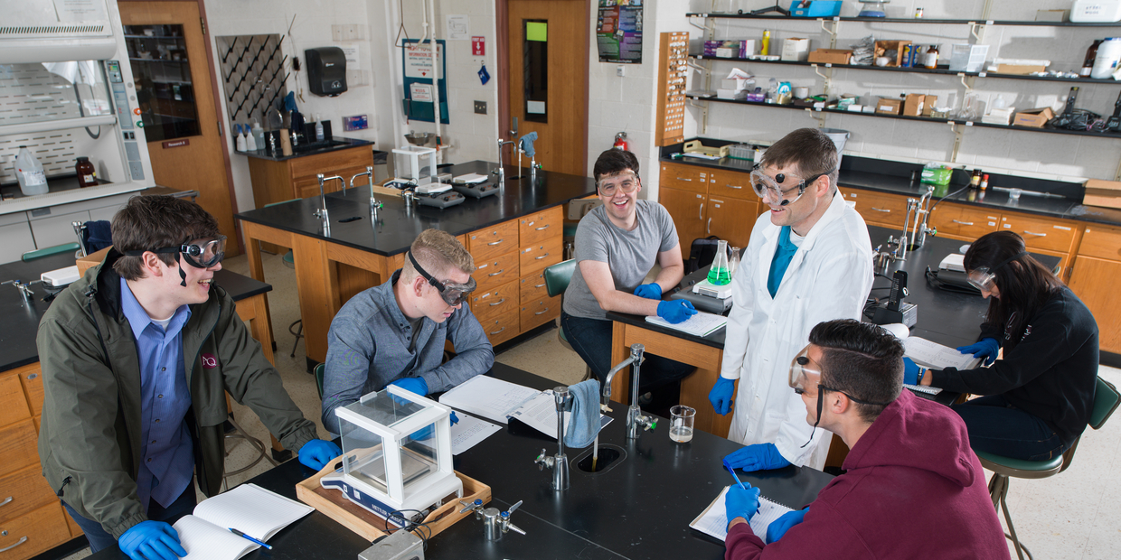 Students laughing in a lab with professor