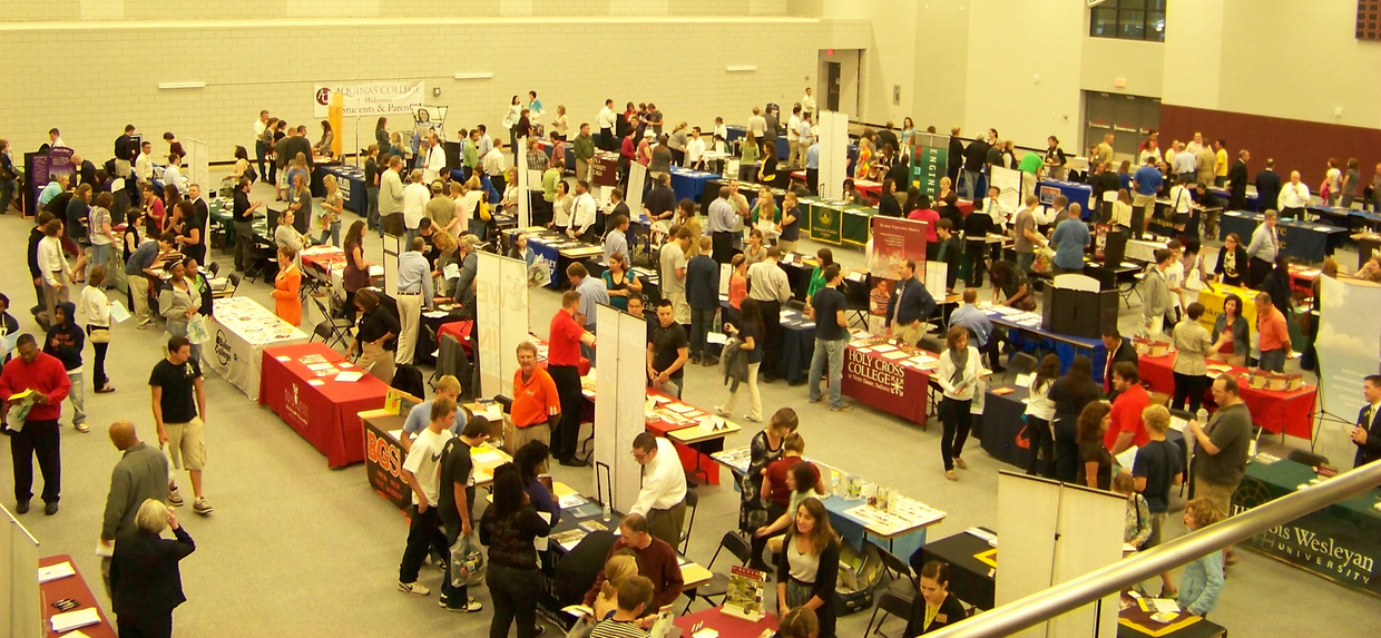 people attending a college fair with tables and signs