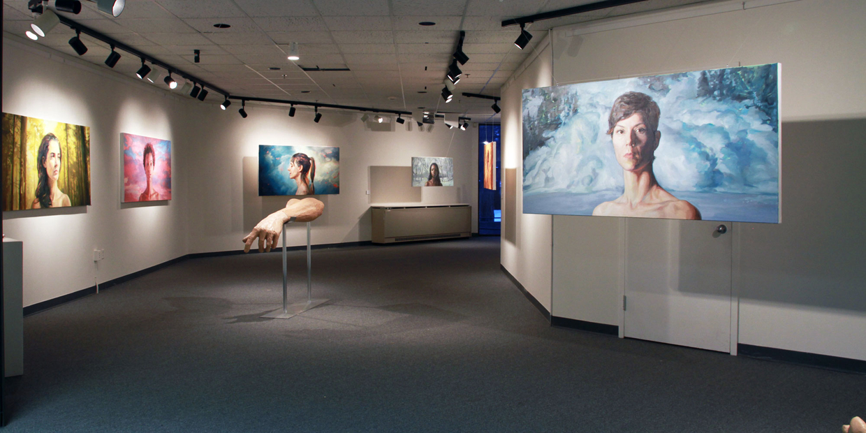 Aquinas art gallery with art in it, paintings of faces and a sculpture of an arm