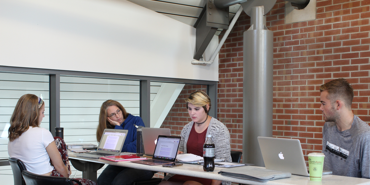 students working on homework at a table in the upper level of the library