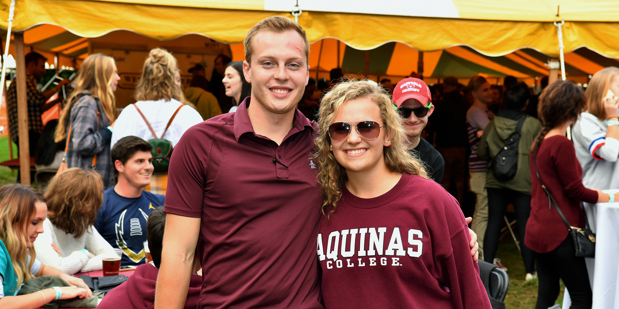 Two students standing in front of tent posing with others in background