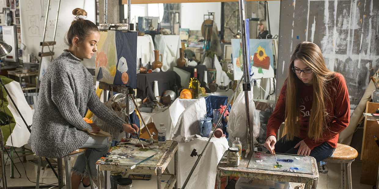 two students in art studio painting