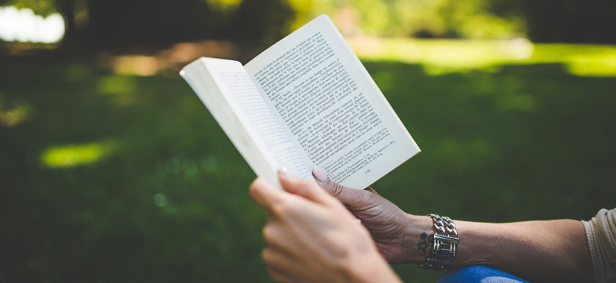 person holding book reading outside