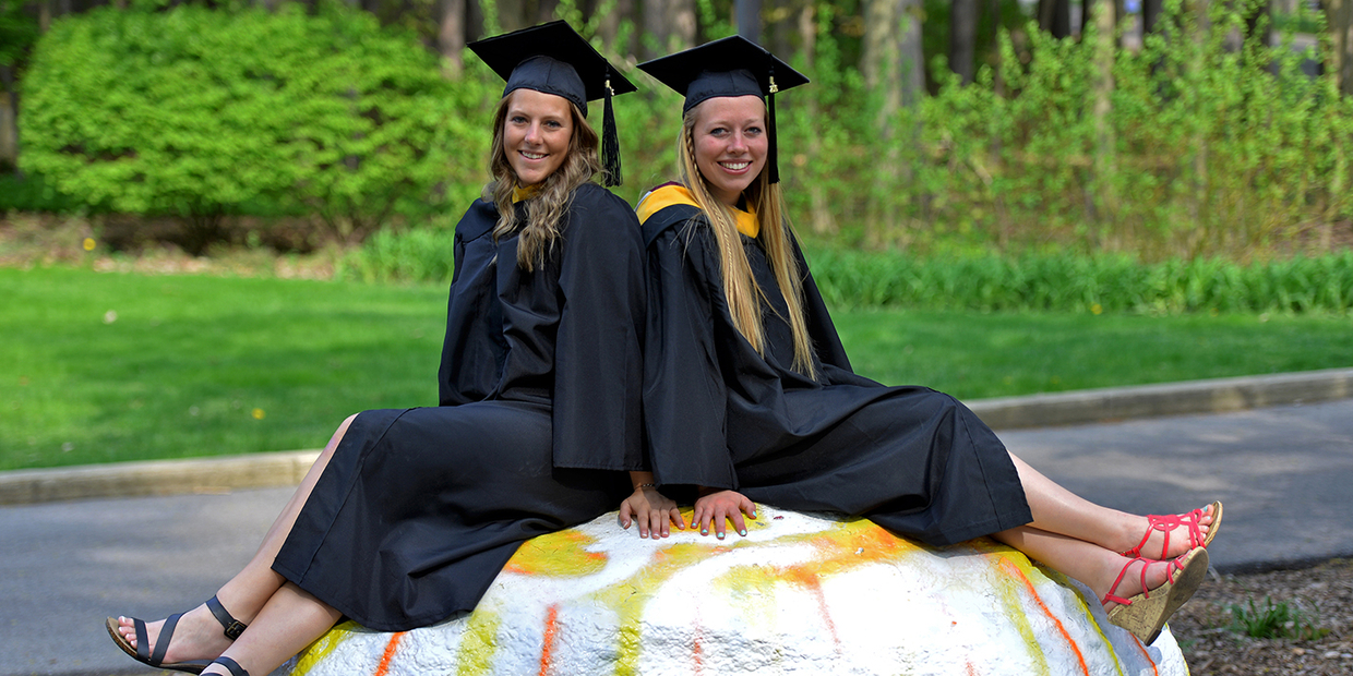 two students with caps and gowns sitting on a rock