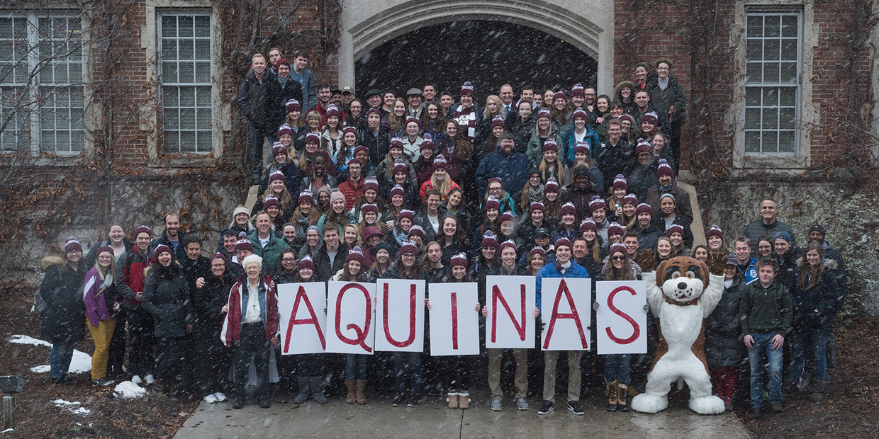 "many students gathered wearing AQ hats holding signs that say ""Aquinas"""