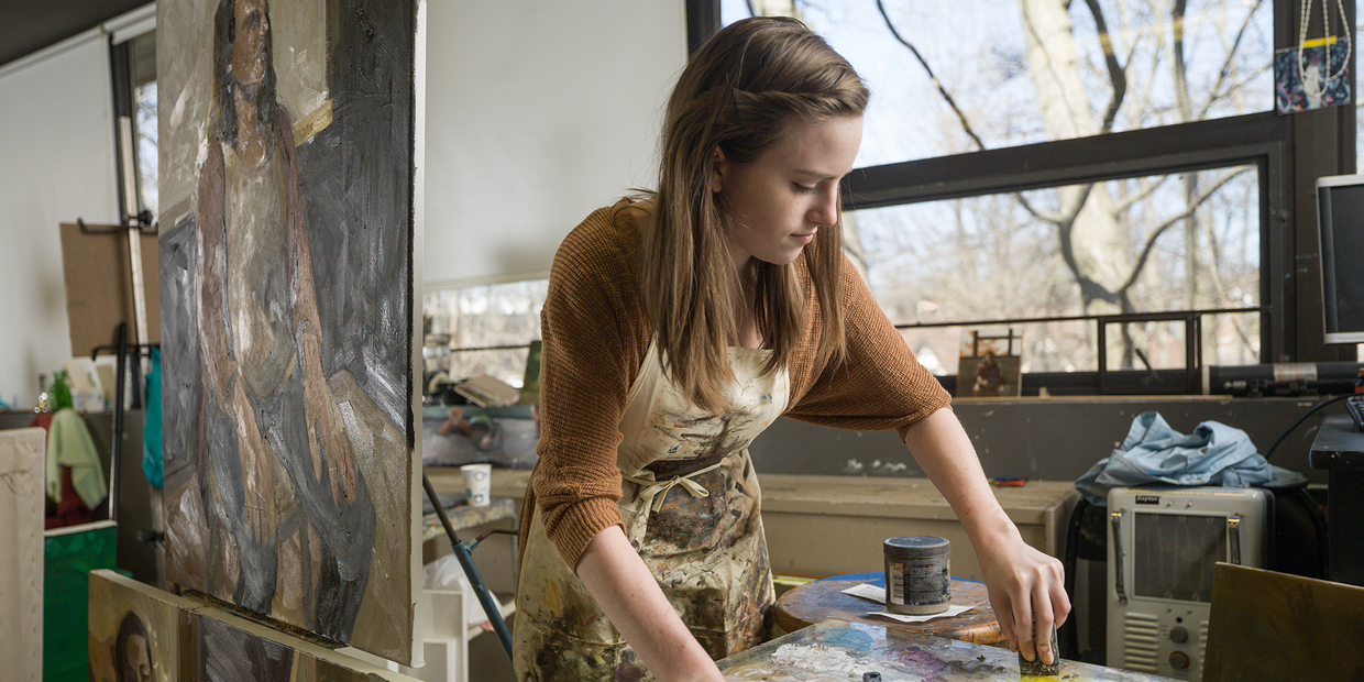 student painting surrounded by art