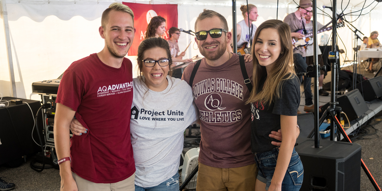 4 adults standing under tent wearing Aquinas gear