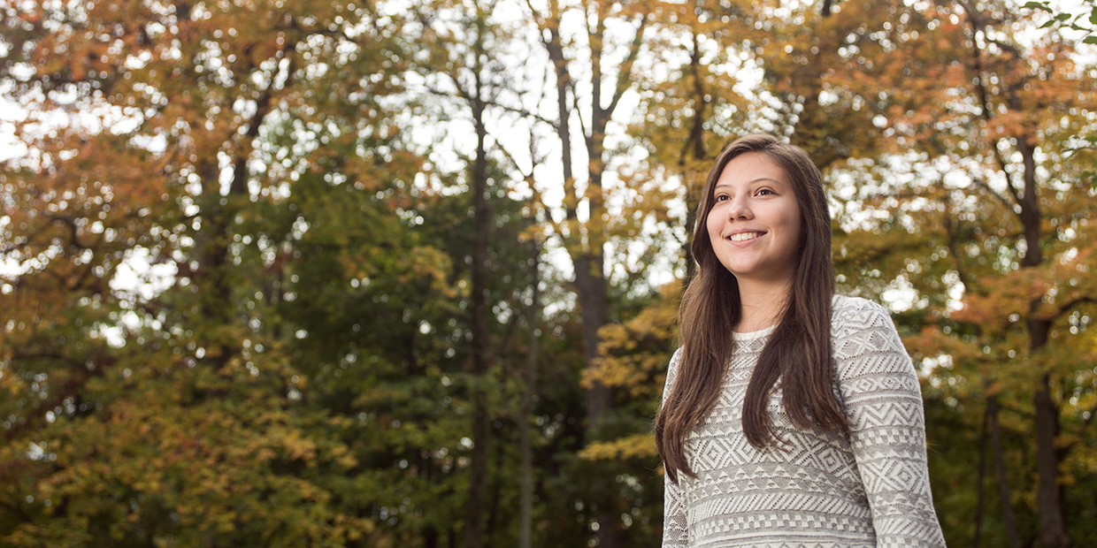 student smiling with trees in the background