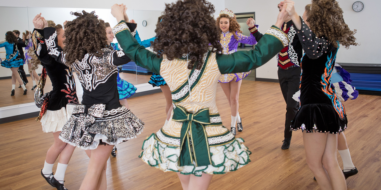 Irish Dancers in bright costumes mid dance