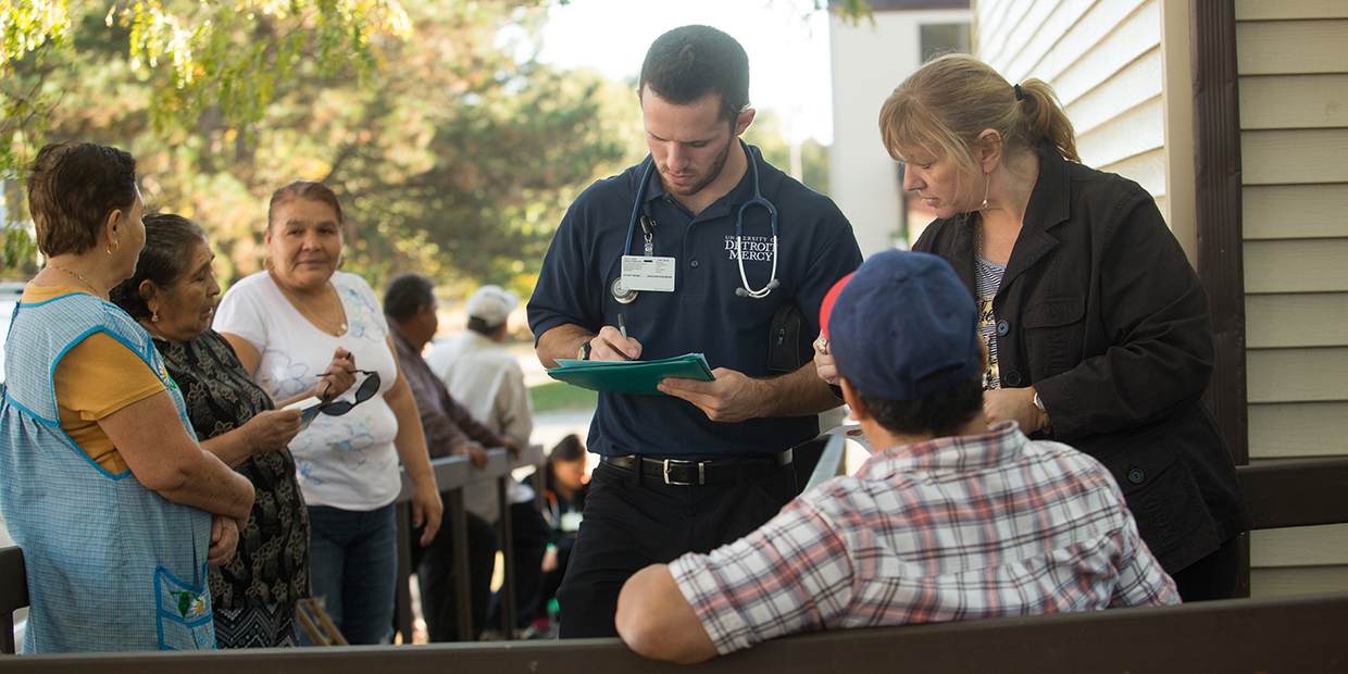 Student nurse talking to man while line of people wait to also talk to him