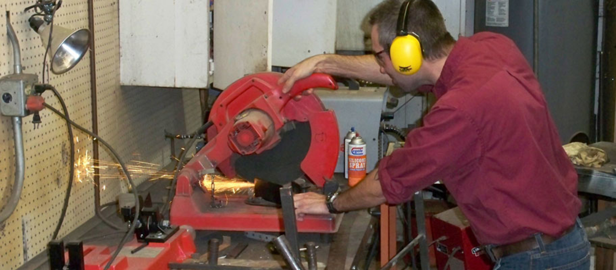 physical plant staff member using a saw