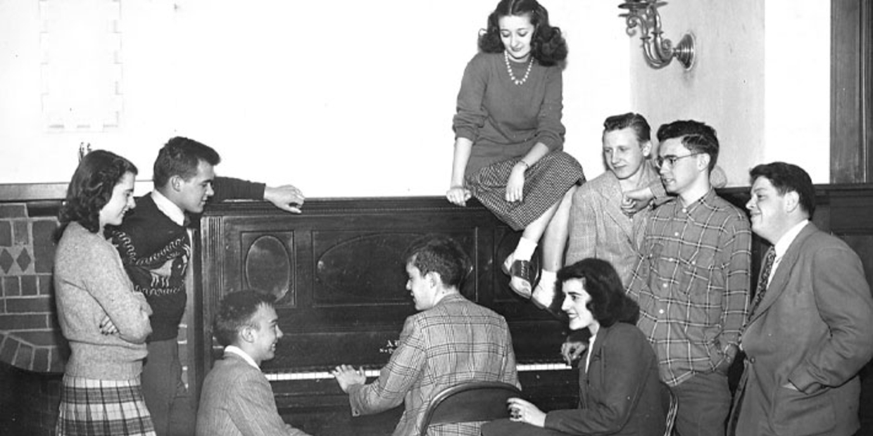 black and white photo of people sitting around a piano