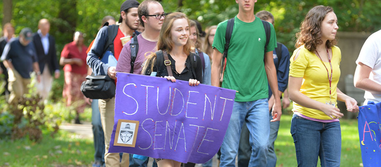 "student holding a purple ""Student Senate"" sign"