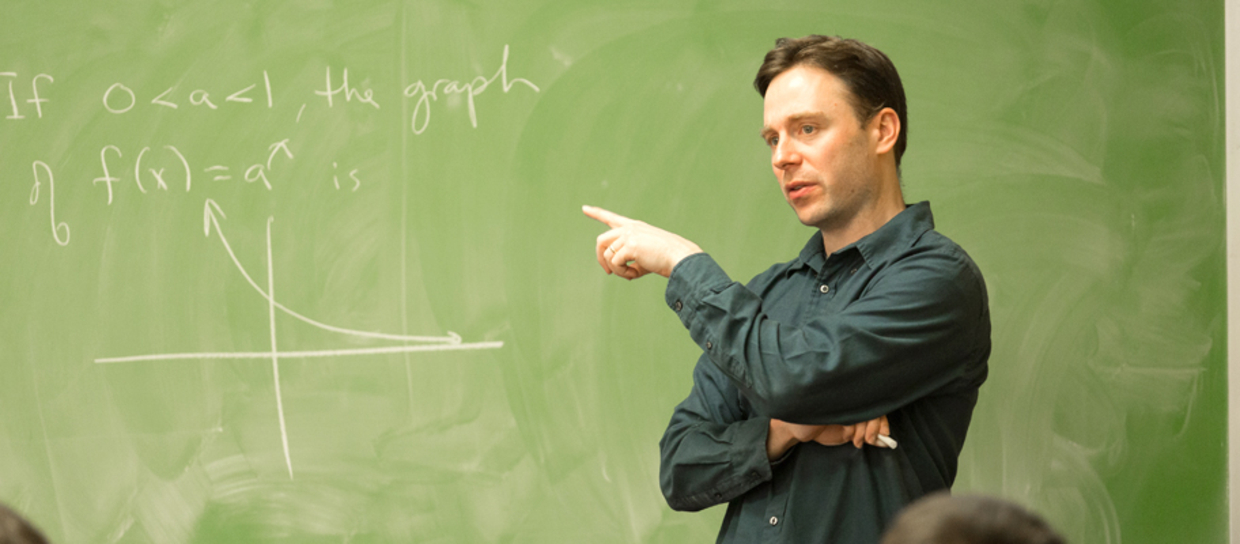 professor teaching math with a green chalkboard