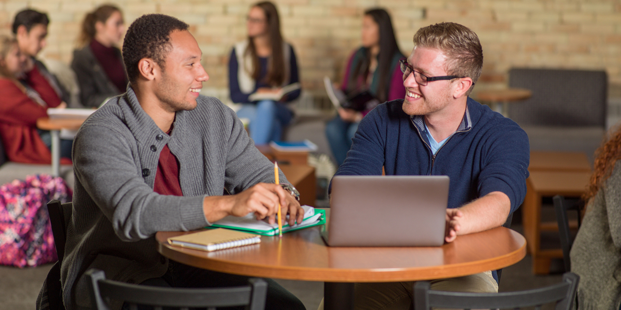 two students at table talking over a laptop