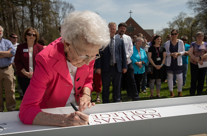 Sister Aquinas signs a white beam outside the campus chapel