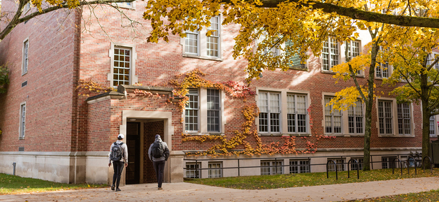 two students walking into the academic building in the fall