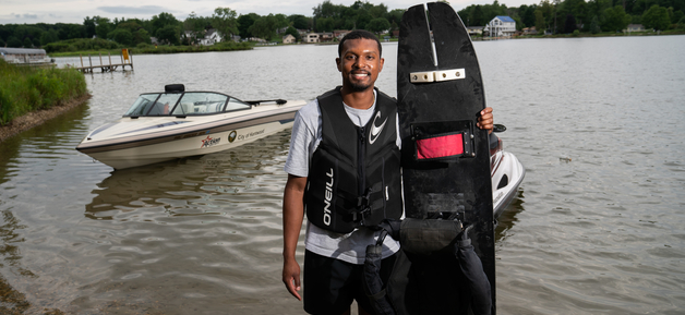 A smiling student wearing a black life vest, white t-shirt and black shorts stands in a lake holding a black adaptive water ski