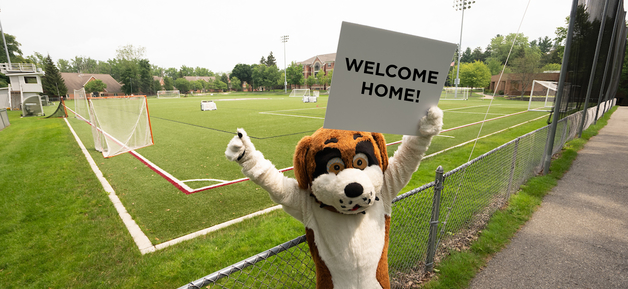 Nelson mascot holding Welcome Home sign in front of Athletic Field